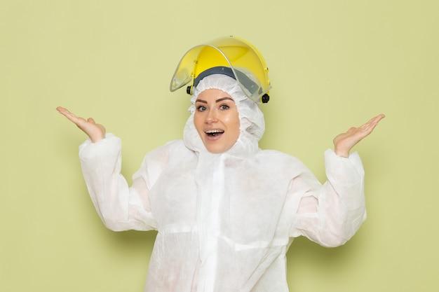 Vooraanzicht jonge vrouw in wit speciaal pak en gele helm poseren met opgetogen uitdrukking op de groene dsk-pak uniforme wetenschap