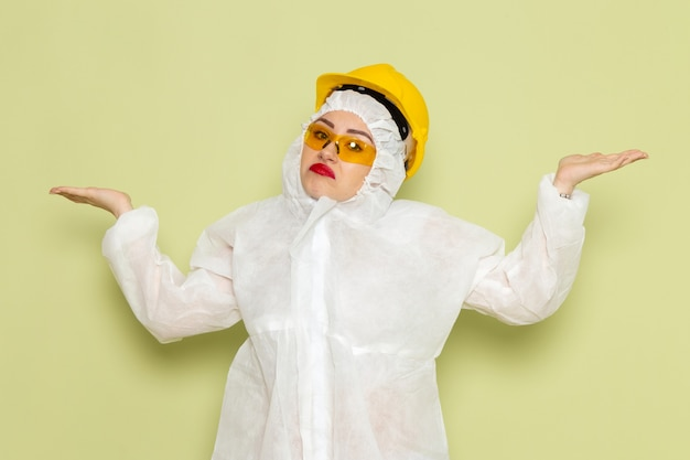 Vooraanzicht jonge vrouw in wit speciaal pak en gele helm poseren met verwarde uitdrukking op de baan van de groene ruimte