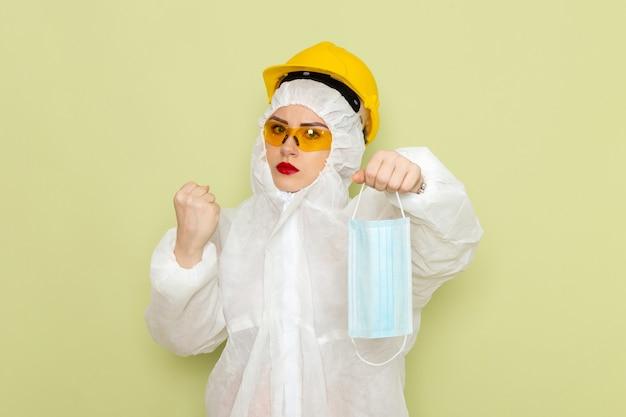Vooraanzicht jonge vrouw in wit speciaal pak en gele helm steriel masker houden op de groene ruimte chemie werk s