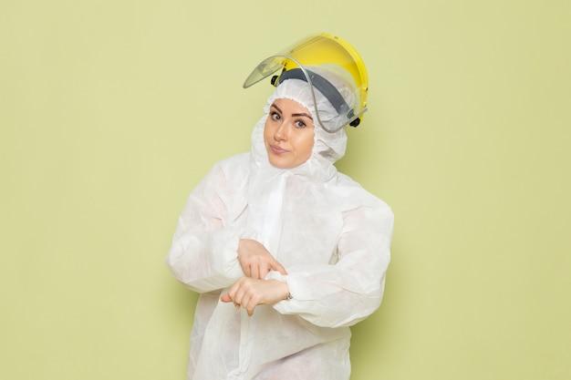 Vooraanzicht jonge vrouw in wit speciaal pak en gele helm wijzend in haar pols op de groene ruimtepak uniforme wetenschap