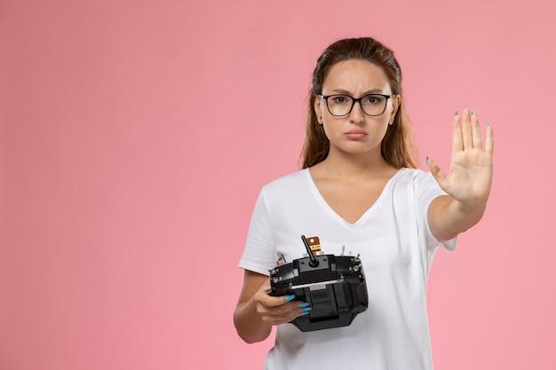 Vooraanzicht jonge vrouw in wit t-shirt met afstandsbediening op de roze achtergrond