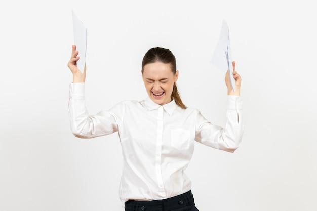 Vooraanzicht jonge vrouw in witte blouse die documenten vasthoudt en zich boos voelt op een witte achtergrond vrouwelijke baanemoties die kantoor voelen