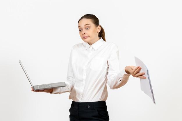 Vooraanzicht jonge vrouw in witte blouse met laptop en documenten op een lichte witte achtergrond vrouwelijke baan kantoor emotie gevoel model
