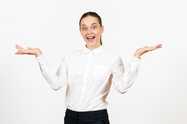 Vooraanzicht jonge vrouw in witte blouse met opgewonden gezicht op witte achtergrond kantoorbaan vrouwelijke emotie gevoel model