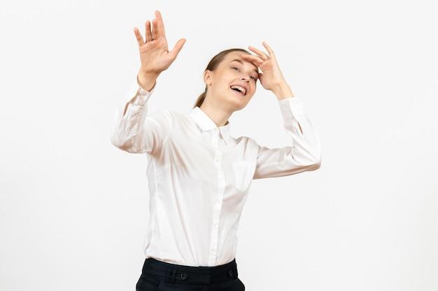 Vooraanzicht jonge vrouw in witte blouse met opgewonden uitdrukking op witte achtergrond vrouwelijk model kantoor emotie baan gevoel