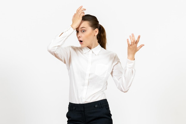 Vooraanzicht jonge vrouw in witte blouse op witte achtergrond kantoorbaan vrouwelijke emoties model voelen
