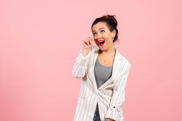 Vooraanzicht jonge vrouw in witte jas poseren op licht roze achtergrond dame mode kleur vrouw emotie fashion