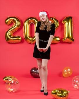 Vooraanzicht jonge vrouw in zwarte jurk ballonnen op rood