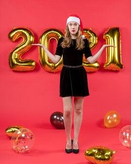 Vooraanzicht jonge vrouw in zwarte jurk die handen ballonnen op rood opent
