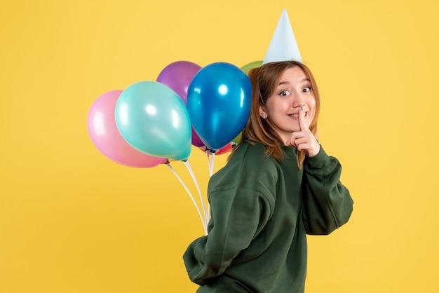 Vooraanzicht jonge vrouw kleurrijke ballonnen achter haar rug verbergen