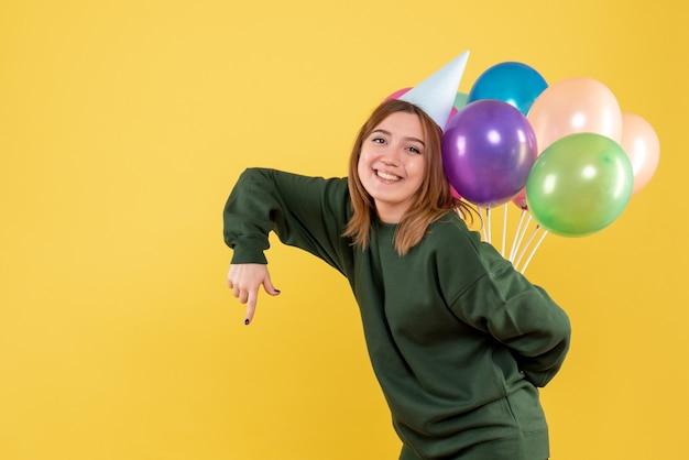 Vooraanzicht jonge vrouw kleurrijke ballonnen verbergen