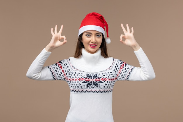 Vooraanzicht jonge vrouw lachend op bruine achtergrond emotie kerst nieuwjaar