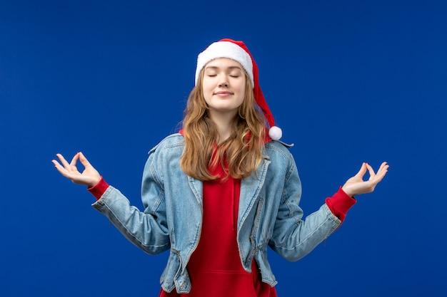 Vooraanzicht jonge vrouw mediteren op blauwe achtergrond emotie kerstvakantie kleur