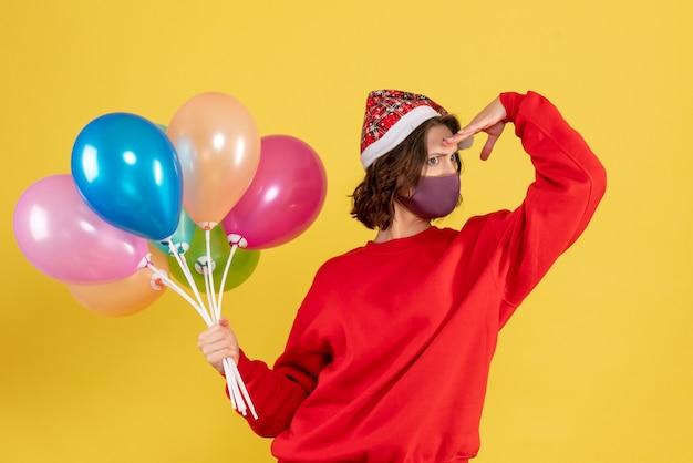 Vooraanzicht jonge vrouw met ballonnen in masker afstand kijken op gele partij emotie nieuwjaar kleur viering vrouw