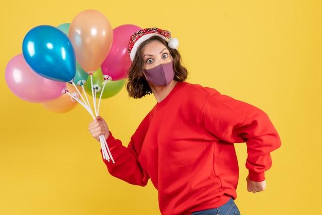 Vooraanzicht jonge vrouw met ballonnen in masker op een gele partij emotie nieuwjaar kleur viering vrouw
