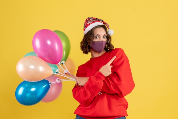 Vooraanzicht jonge vrouw met ballonnen op geel