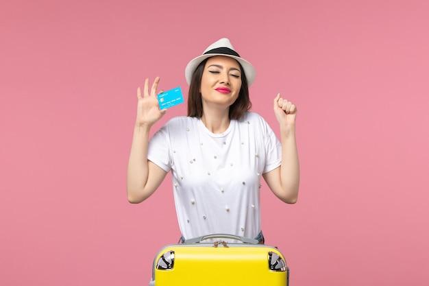 Vooraanzicht jonge vrouw met bankkaart op de roze muur vrouw reis zomerreis