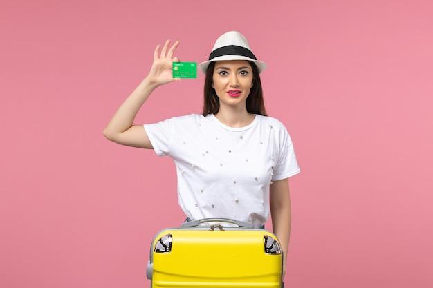 Vooraanzicht jonge vrouw met bankkaart op de roze muur zomerreis emotie vrouw