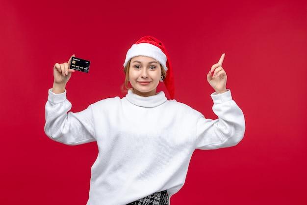 Vooraanzicht jonge vrouw met bankkaart op lichtrode achtergrond