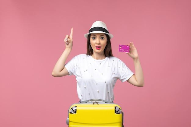 Vooraanzicht jonge vrouw met bankkaart op lichtroze muur vakantie geld vrouw trip