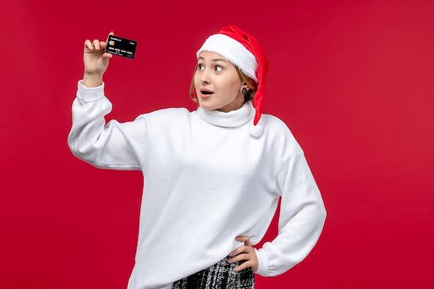 Vooraanzicht jonge vrouw met bankkaart op rode achtergrond