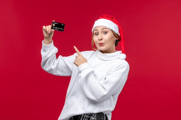 Vooraanzicht jonge vrouw met bankkaart op rood bureau