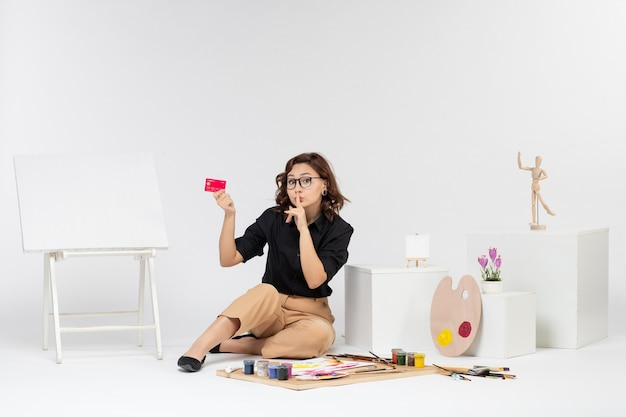 Vooraanzicht jonge vrouw met bankkaart op witte achtergrond