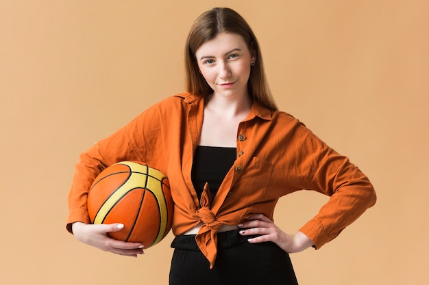 Vooraanzicht jonge vrouw met basketbalbal