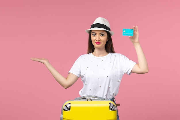 Vooraanzicht jonge vrouw met blauwe bankkaart op de reisreis met roze muurkleur