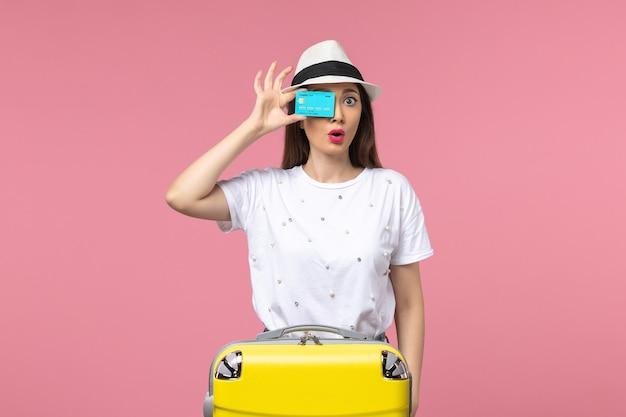 Vooraanzicht jonge vrouw met blauwe bankkaart op de roze muur vrouw reis geld reis
