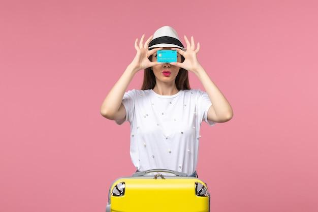 Vooraanzicht jonge vrouw met blauwe bankkaart op lichtroze muur vrouw reis geld reis