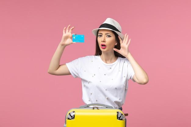 Vooraanzicht jonge vrouw met blauwe bankkaart op lichtroze muurreis kleur reis zomer