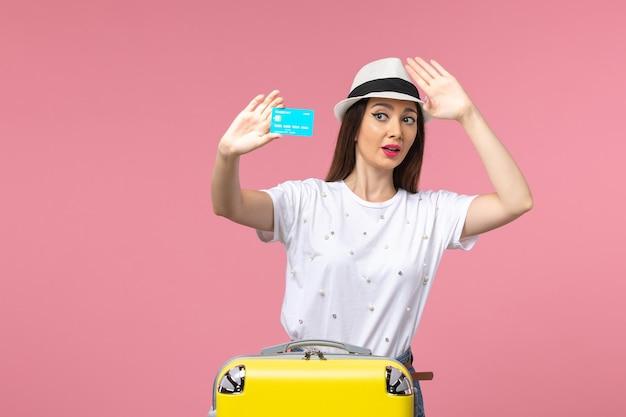 Vooraanzicht jonge vrouw met blauwe bankkaart op roze muur reis reis zomer
