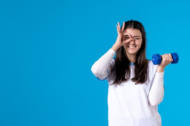 Vooraanzicht jonge vrouw met blauwe halter op blauwe muur