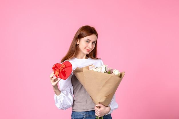 Vooraanzicht jonge vrouw met bloemen en heden als de daggift van de vrouw op roze achtergrond horizontale maart gelijkheid liefde sensuele datum roze vrouw