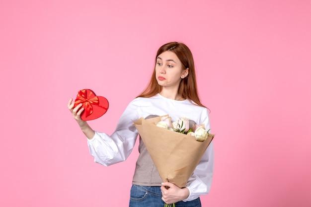 Vooraanzicht jonge vrouw met bloemen en heden als de daggift van de vrouw op roze achtergrond horizontale maart gelijkheid sensuele vrouwelijke roze vrouw liefde