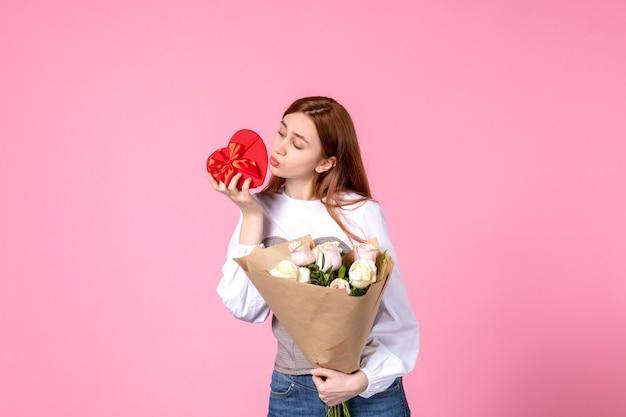 Vooraanzicht jonge vrouw met bloemen en heden als de daggift van de vrouw op roze achtergrond horizontale maart gelijkheid vrouwelijke datum vrouw liefde sensueel