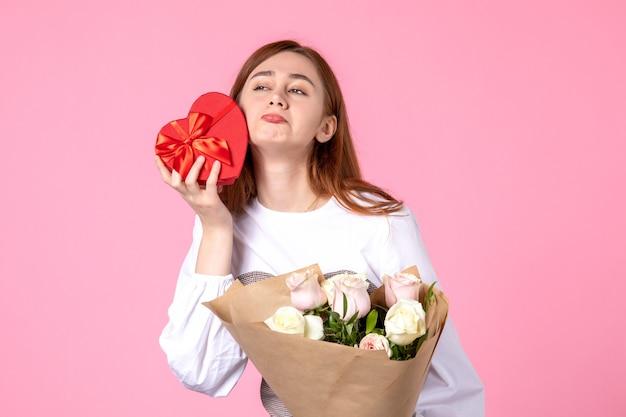 Vooraanzicht jonge vrouw met bloemen en heden als de daggift van de vrouw op roze achtergrond horizontale maart gelijkheidsdatum roos vrouw liefde sensueel