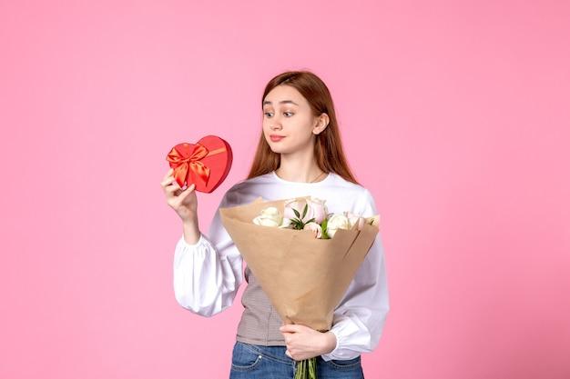 Vooraanzicht jonge vrouw met bloemen en heden als de daggift van de vrouw op roze achtergrond horizontale maart vrouw datum roos liefde sensueel vrouwelijk