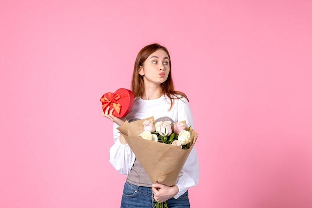 Vooraanzicht jonge vrouw met bloemen en heden als de daggift van de vrouw op roze achtergrond steeg horizontale maart vrouwelijke datum vrouw sensuele gelijkheid