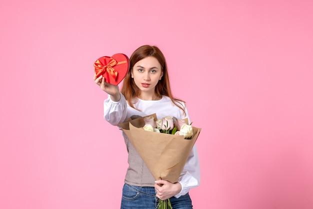 Vooraanzicht jonge vrouw met bloemen en heden als de gift van de dag van de vrouw op roze achtergrond steeg maart vrouwelijke datum vrouw liefde sensuele gelijkheid horizontaal