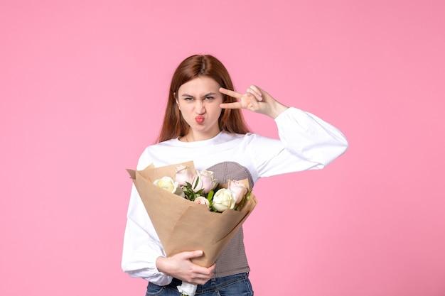 Vooraanzicht jonge vrouw met boeket van mooie rozen op pinks