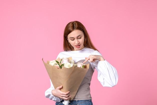 Vooraanzicht jonge vrouw met boeket van mooie rozen op roze maart parfum