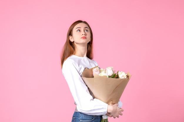 Vooraanzicht jonge vrouw met boeket van mooie rozen op roze