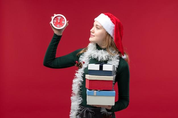 Vooraanzicht jonge vrouw met cadeautjes en klok op rode achtergrond