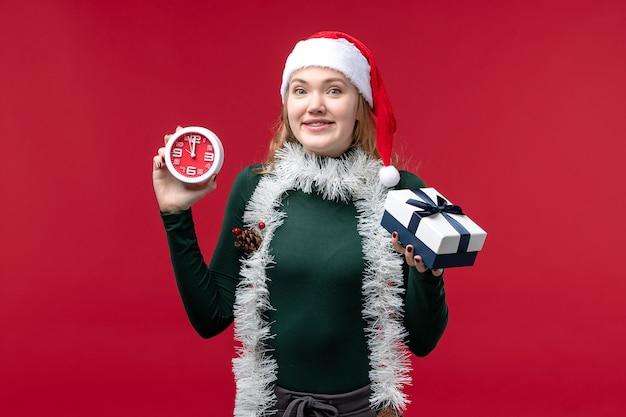 Vooraanzicht jonge vrouw met cadeautjes met klok op rode vloer rode nieuwjaarsvakantie