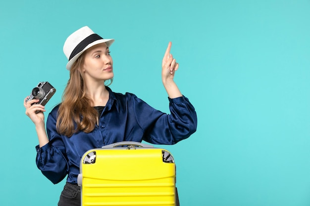 Vooraanzicht jonge vrouw met camera en lachend op lichtblauwe achtergrond vrouw reis zeereis vliegtuig