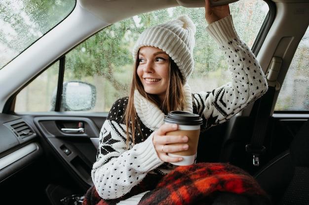 Vooraanzicht jonge vrouw met een kopje koffie in de auto