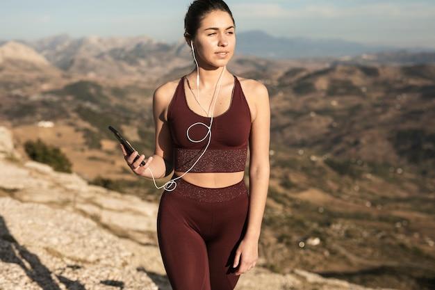 Vooraanzicht jonge vrouw met een koptelefoon en telefoon