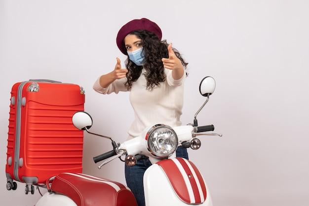 Vooraanzicht jonge vrouw met fiets in masker op witte achtergrond virus voertuigsnelheid covid- motorfiets wegkleur